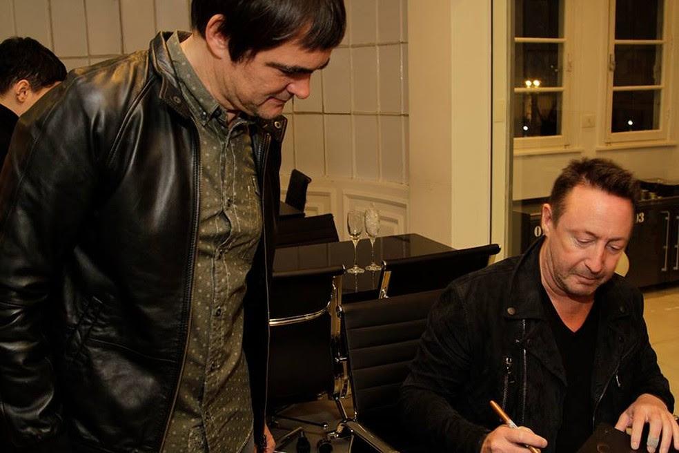 Julian Lennon autografa livro de exposição para Samuel Rosa, do Skank, em coquetel de abertura em SP (Foto: Divulgação / Leica Gallery São Paulo)