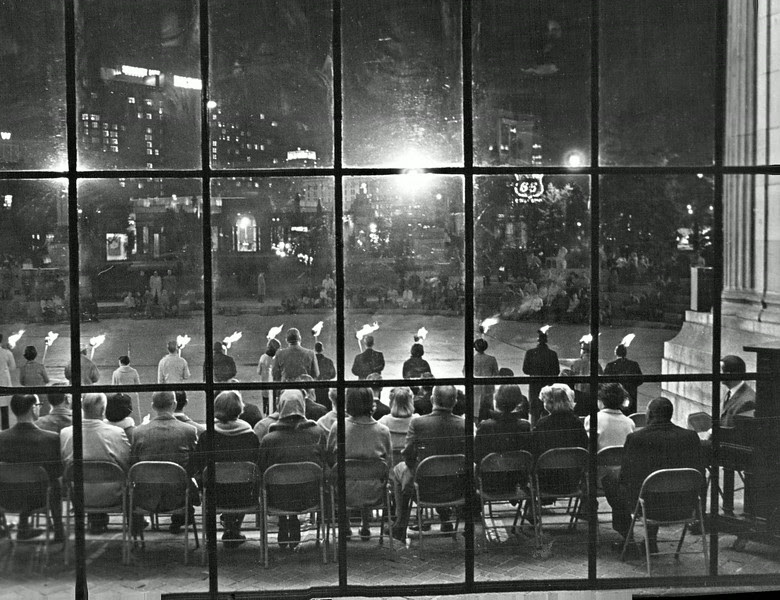 "Description of  NOV 17 1965 - The Civic Center assembly, from behind the platform, shows the choir in the foreground and torch bearers beyond at the Wednesday night ceremony. The Denver Religious Council on Human Relations gave homage to ""martyrs"" in the civil rights cause during the hour-long meeting in which some 350 persons, including clergy, participated on a chilly night in downtown Denver. (Duane Howell/The Denver Post)"