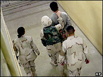 A US military intelligence officer leads an Iraqi prisoner at Abu Ghraib