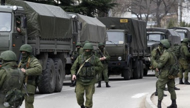 Armed servicemen wait near Russian army vehicles outside a Ukrainian border guard post in the Crimean town of Balaclava March 1, 2014. REUTERS/Baz Ratner