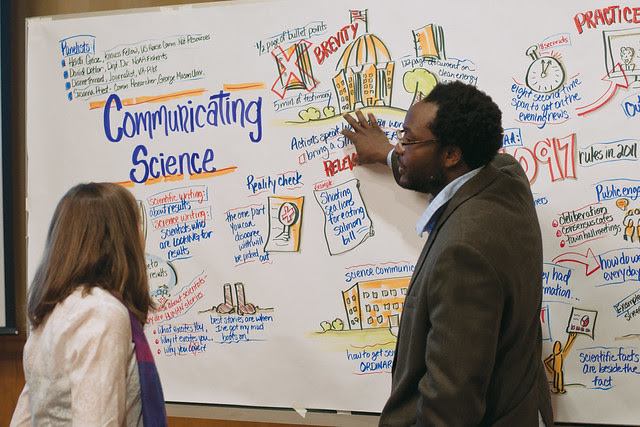 Anu Frank-Lawale (right) and a VIMS student (left) discuss the graphic facilitation that Julie Stuart did during the communicating science panel. ©Will Sweatt/VASG