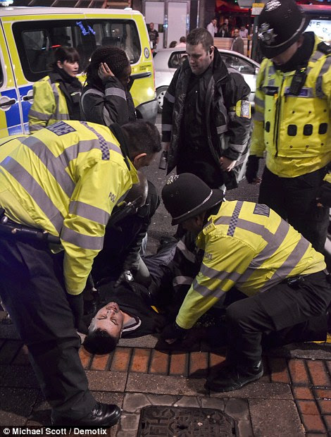 A man is wrestled to the ground by police and security after allegedly assaulting a security guard, he was later arrested and taken away in a police van, witnesses said