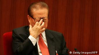 Former President Jiang Zemin adjusts his glasses at the opening session of the ruling Communist Party's five-yearly congress, 15 October 2007 at the Great Hall of the People in Beijing. President Hu Jintao opened China's biggest political event with pledges to curb the worst excesses of breakneck economic growth and implement cautious political reforms while addressing the ruling Communist Party's elite, gathered for their five-yearly Congress, with Hu acknowledging that China's modernisation drive since the late 1970s had also caused huge environmental and social problems. AFP PHOTO/Frederic J. BROWN (Photo credit should read FREDERIC J. BROWN/AFP/Getty Images)