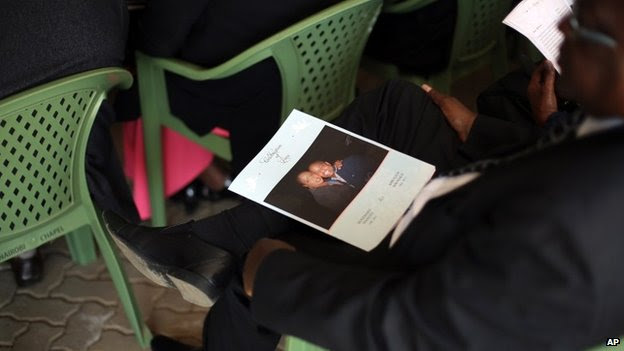 A man sits with the service leaflet during the funeral of Mbugua Mwangi and his fiancee Rosemary Wahito, in Nairobi, Kenya, Friday 27 September 2013