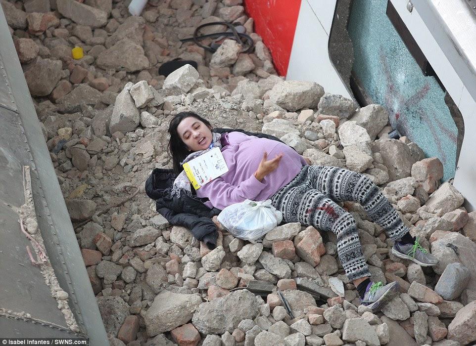 Θύμα: Ένας ηθοποιός προσποιείται ότι είναι μια έγκυος γυναίκα τραυματίστηκε στην καταστροφή ψέματα που περιμένουν να διασωθούν σε ένα σωρό από μπάζα