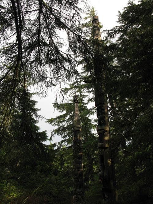 a peek at totems of Kasaan Totem Park through trees, Kasaan, Alaska