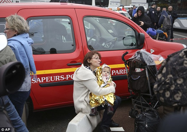 A woman clasps a young child after being evacuated from the terminal during this morning's attack