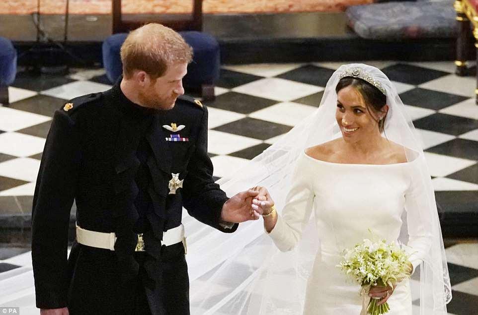 Harry y Meghan se toman de la mano cuando salen de la capilla de San Jorge después de la ceremonia de la boda