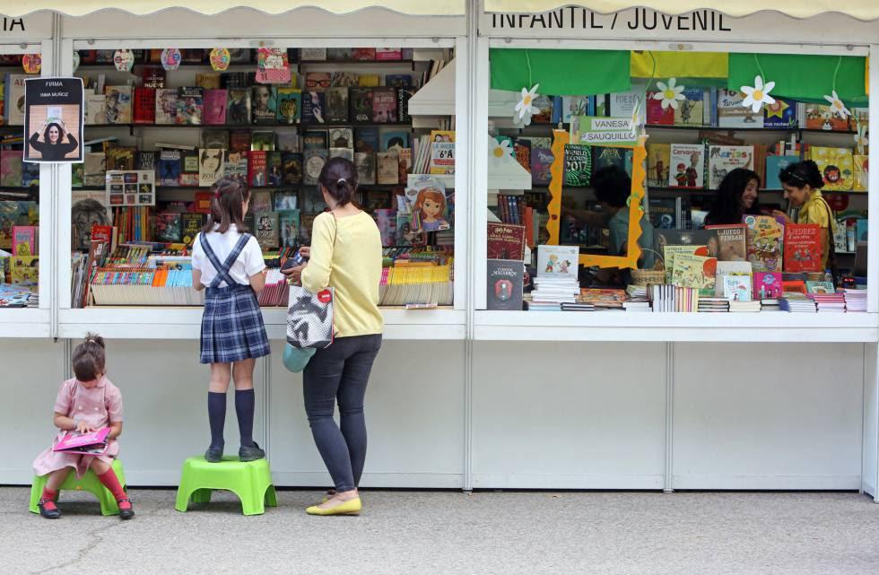 Dos niñas hojean libros en la Feria del Libro de Madrid.