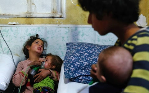 A Syrian girl holds an oxygen mask over the face of an infant at a make-shift hospital following a reported gas attack