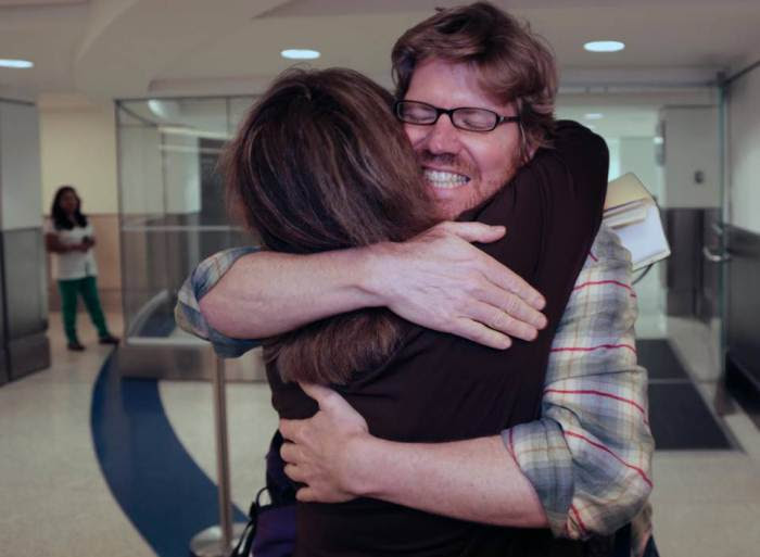 Original Caption: Colleague Luisa Yanez, left, gives Jim Wyss, a welcome hug upon his arrival. Miami Herald reporter Jim Wyss arrived at Miami International Airport after being detained by Venezuela for three days on Sunday, November 10, 2013. MIAMI HERALD STAFF