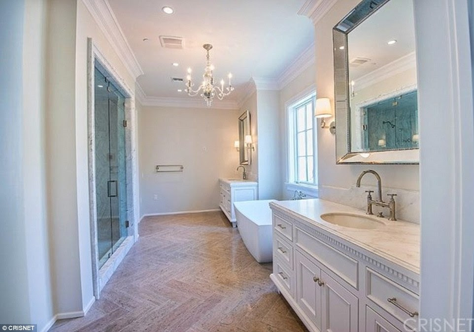 Luxurious: The bathroom includes a large rub, a crystal chandelier and a walk in shower