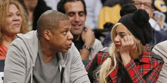Entrepreneur and musician Jay Z, left, sits with his wife, singer Beyonce during the Brooklyn Nets NBA basketball game against the Philadelphia 76ers at the Barclays Center, Monday, Feb. 3, 2014 in New York. (AP Photo/Kathy Willens)