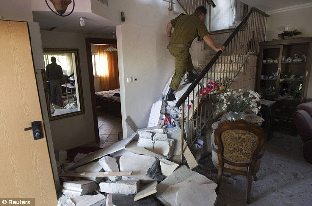 Checking for casualties: An Israeli soldier walks up the steps of a house damaged by a rocket. U.S. Secretary of State Hillary Clinton headed to the region with a message that escalation of the week-long conflict was in nobody's interest