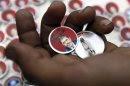 """Badges showing an image of Egypt's President Mohamed Mursi and the words """"Yes to constitution"""" are displayed at a street stall outside Al Azhar mosque in old Cairo"""