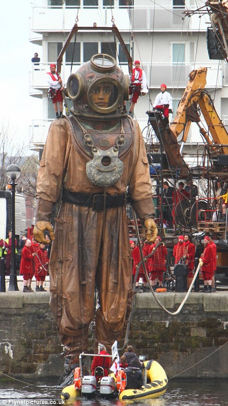On his way: The diver puppet emerges at the city waterfront and begins his journey to find the Little Girl Giant, based on a real-life girl who lost her father on the Titanic
