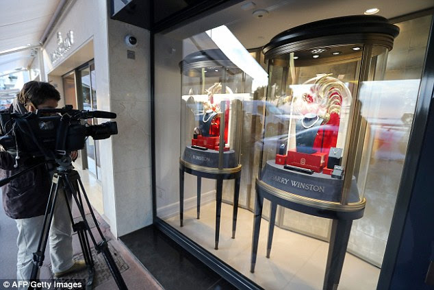 A cameraman films the front of the Harry Winston store in Cannes after yesterday's robbery