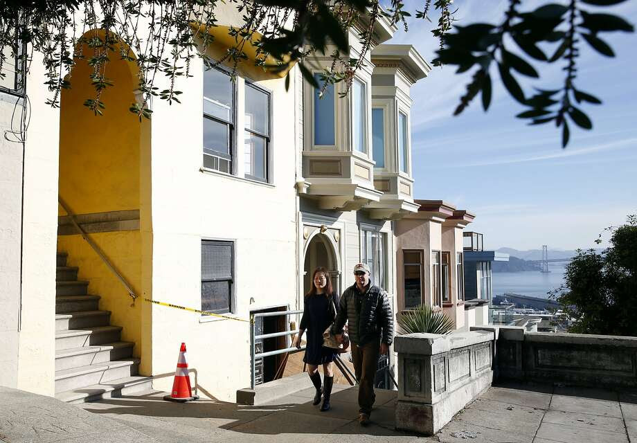Michelle Huang and Thomas Payne walk past the building on Vallejo Street in San Francisco where they own three units. They are embroiled in a complex feud with the owner of one of the other units. Photo: Paul Chinn, The Chronicle