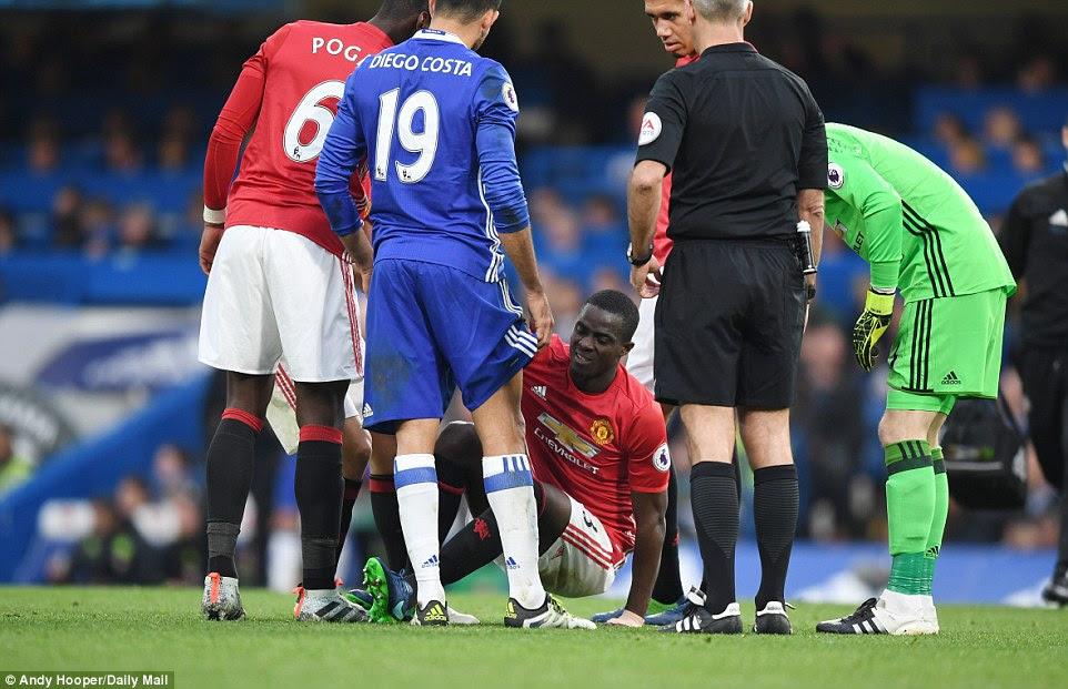 Bailly (centre) is checked upon by his United and Chelsea players after suffering an injury during the match