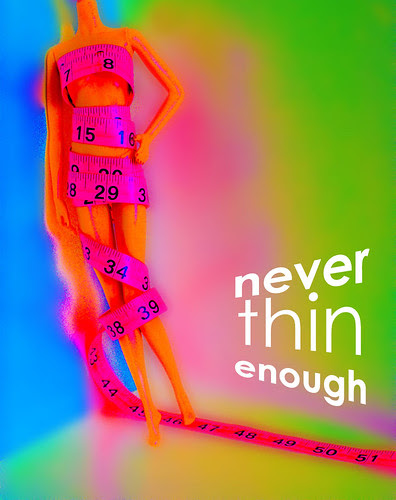 Never Thin Enough: a Model Muse body Barbie wrapped in hot pink measuring tape