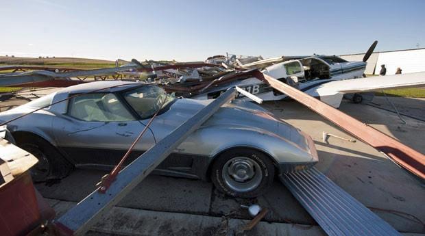 Um tornado que atingiu a cidade de Wayne, no Nebraska, nesta sexta-feira (5) causou prejuízo de milhões de dólares. Na imagem, é possível ver destroços sobre um corvette e uma aeronave de pequeno porte. De acordo com o prefeito, não houve mortes e houve poucos feridos. (Foto: Dave Weaver/AP)
