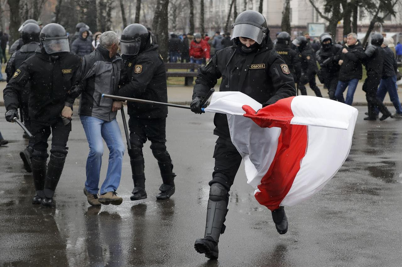 A Belarus policeman runs with an opposition flag as other detain a protester during an opposition rally in Minsk, Belarus, Saturday, March 25, 2017. A cordon of club-wielding police blocked the demonstrators' movement along Minsk's main avenue near the Academy of Science. Hulking police detention trucks were deployed in the city center.