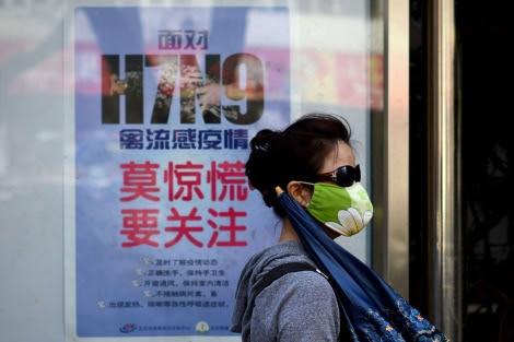 Una mujer pasea con una mascarilla en una calle de Pekín.   Afp