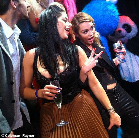 Cool cat: Miley flashes a peace sign as she gets into the party spirit with a friend