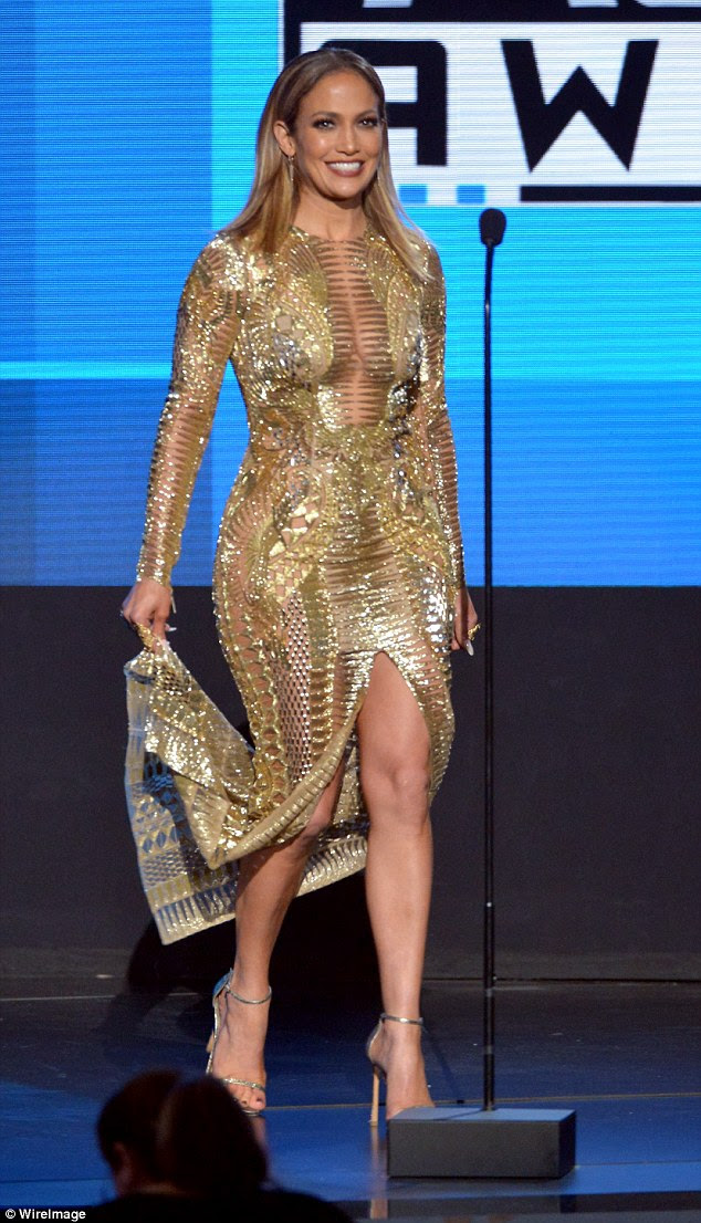 Look number four: J.Lo held her train as she donned a shimmering, form-fitting golden gown for her next look
