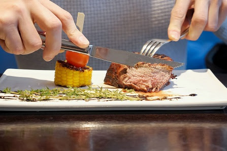 Close-up view of a man cutting off a piece of steak.