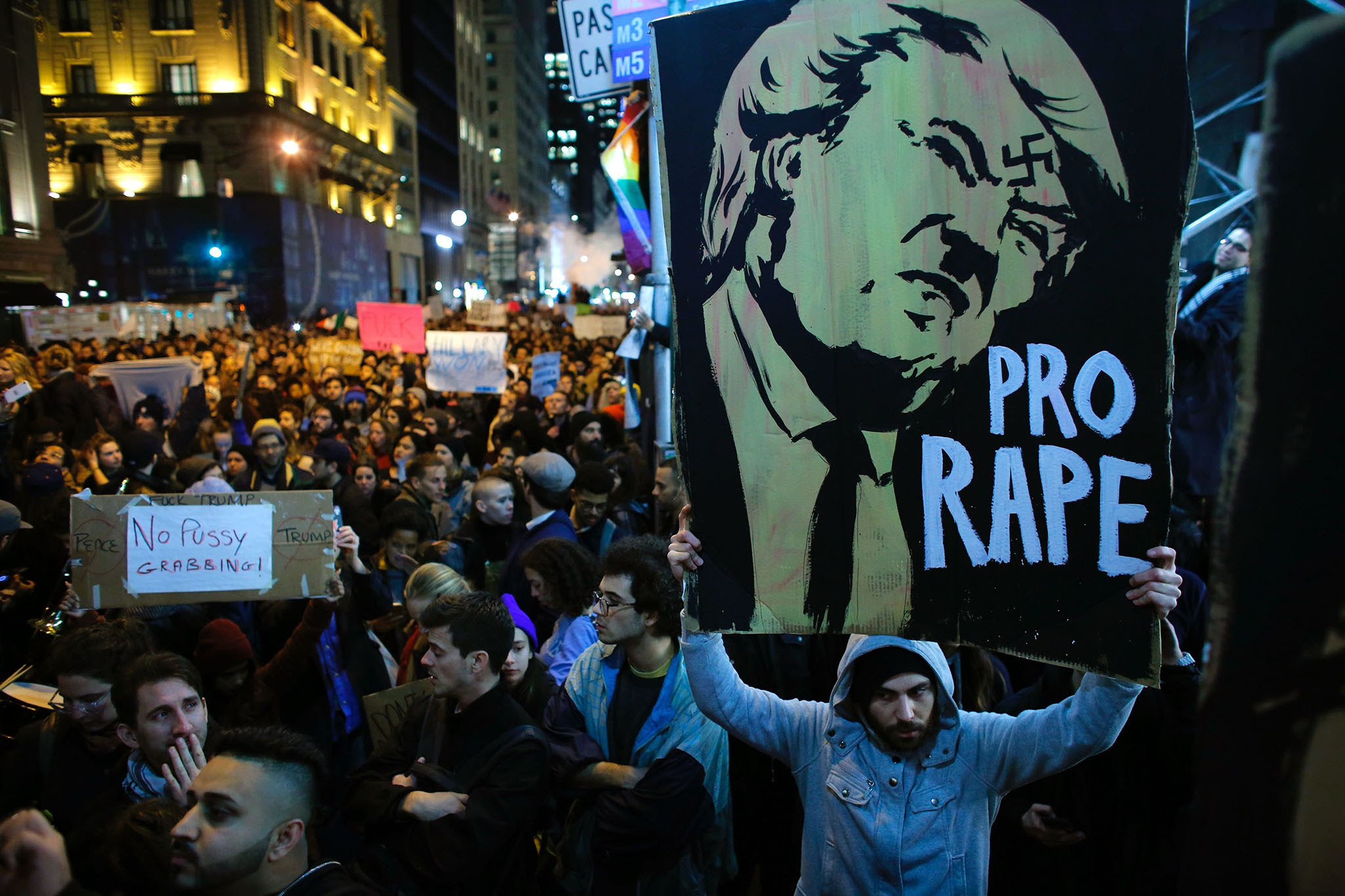 A man holds a poster as she takes part in a protest against President-elect Donald Trump in New York City on November 9, 2016. / AFP PHOTO / KENA BETANCURKENA BETANCUR/AFP/Getty Images