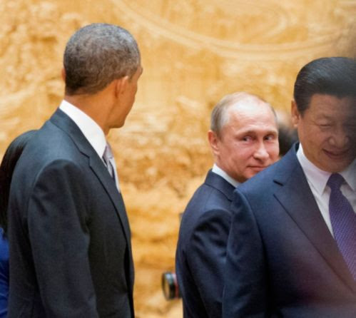 Russian President Vladimir Putin, center, looks back at U.S. President Barack Obama, left, as they arrive with Chinese President Xi Jinping, right, at the the Asia-Pacific Economic Cooperation (APEC) Summit plenary session at the International Convention Center, Yanqi, Tuesday, Nov. 11, 2014 in Beijing.