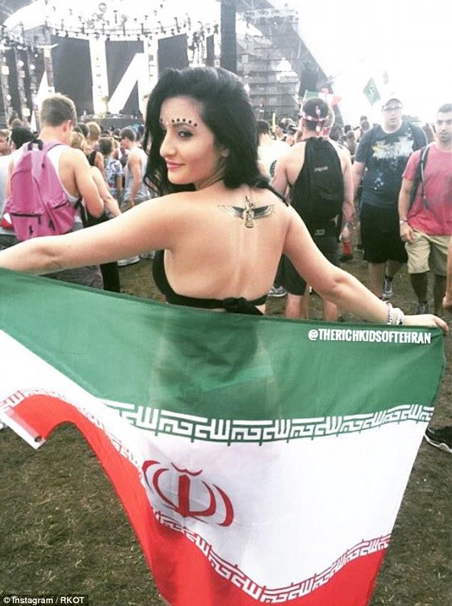 Uma mulheres jovens seminuas detém a bandeira iraniana, enquanto Partes em um festival de música