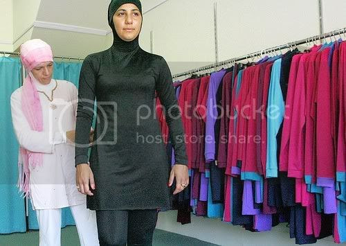 Muslim fashion designer Aheda Zanetti (L) makes adjustments  to her Islamic swimsuit worn by Australian model Mecca Laalaa (R) at  her shop in Sydney, 12 January 2007 (AFP, AFP/Getty Images / January 12,  2007)