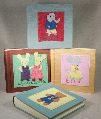 four handmade photo albums with cute felt pictures on the cover
