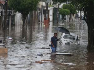 Homem tenta atravessar região alagada pela chuva na Avenida Zaki Narchi, altura da Rua Urupiara, na Zona Norte de São Paulo, no final da tarde desta sexta-feira (24). (Foto: Alex Silva/Estadão Conteúdo)