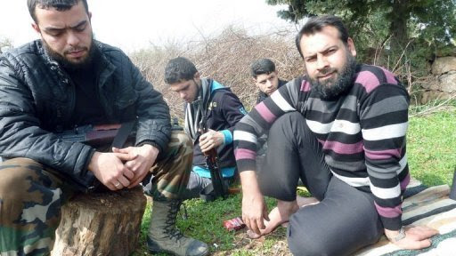 """Abu Mahmoud (R), a respected rebel leader, sits on a rug placed on the grass at his home in Atme, in the northwestern Syrian province of Idlib, on February 10, 2013. """"The real revolution in Syria is over, we have been betrayed,"""" laments a bitter Abu Mahmoud, accusing fellow commanders of marring a """"beautiful"""" revolt through corruption"""