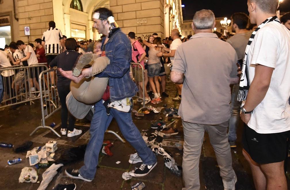 Homem carrega pessoa ferida em correira durante a final da Champions League neste sábado (3) em praça da Itália (Foto: REUTERS/Giorgio Perottino)