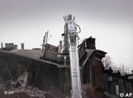 Ein Haus  wird mit einem Bagger zerstört (Foto: AP)