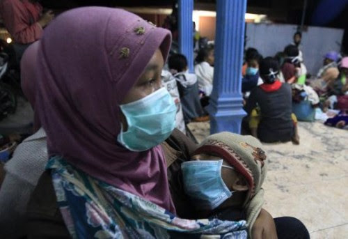 A villager who was evacuated from her home due to Mount Kelud's eruptions, holds her daughter at a temporary shelter at Sumber Agung village in Kediri