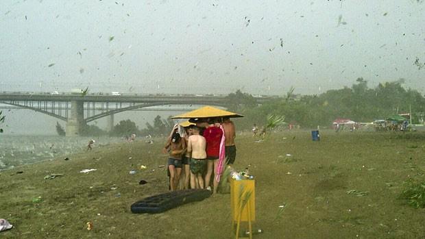 Banhistas se abrigam de chuva de granizo (Foto: AP Photo/Nikita Dudnik)
