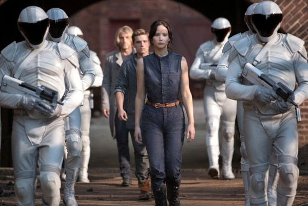 Katniss Everdeen (Jennifer Lawrence), Peeta Mellark (Josh Hutcherson) and Haymitch Abernathy (Woody Harrelson) are surrounded by Peacekeepers in THE HUNGER GAMES: CATCHING FIRE.