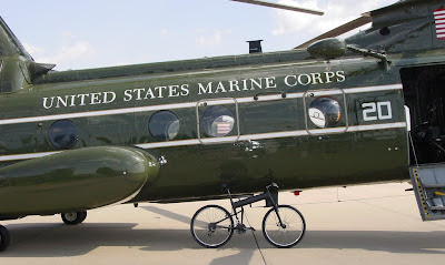 Image of folding bicycle next to Marines Corps helicopter