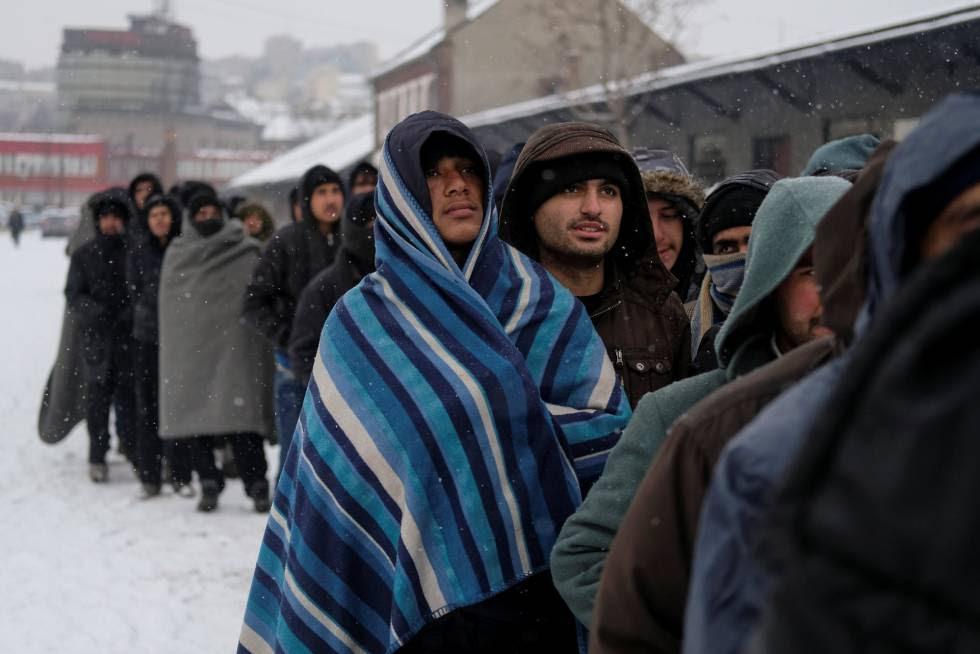 Refugiados esperan un plato de comida en un almacén aduanero en Belgrado (Serbia).