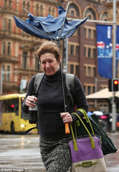 SYDNEY, AUSTRALIA - APRIL 21: A woman walks in the CBD with a broken umbrella on April 21, 2015 in Sydney, Australia. A second day of damaging winds and heavy rain have hit the New South Wales coast, dowing powerlines, cutting power to homes and causing delays for traffic and public transport.  (Photo by Brendon Thorne/Getty Images)