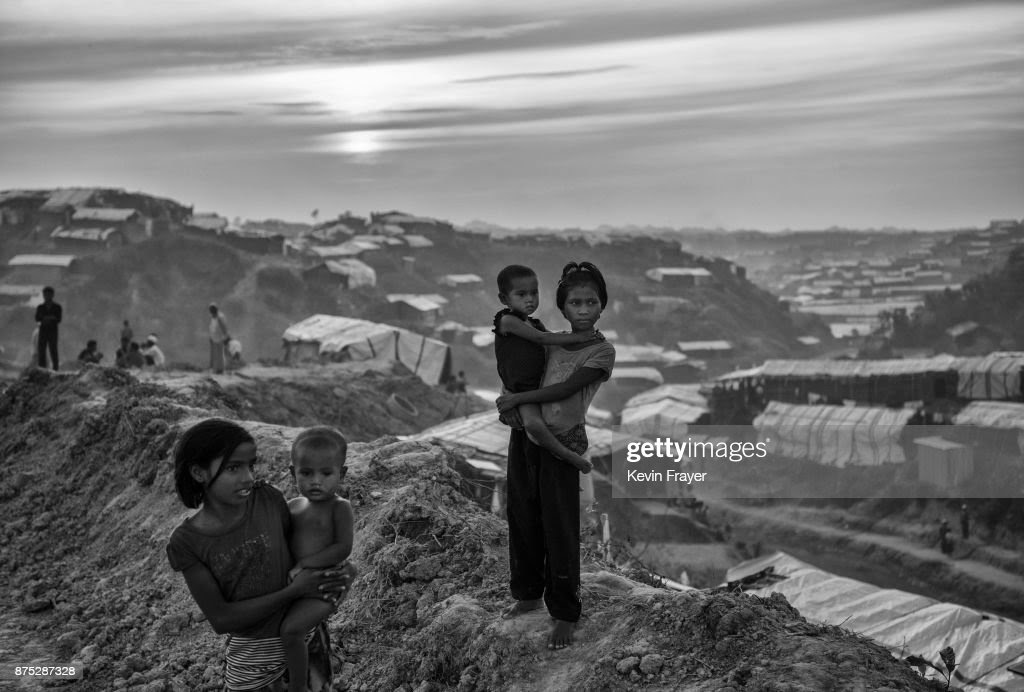 COX'S BAZAR, BANGLADESH - OCTOBER 28: Rohingya refugee children stand on a new road being built on October 28, 2017 at the Balukhali refugee camp near Cox's Bazar, Bangladesh. More than 600,000 Rohingya refugees have flooded into Bangladesh to flee an offensive by Myanmar's military that the United Nations has called 'a textbook example of ethnic cleansing'. The refugee population continues to swell further, with thousands more Rohingya Muslims making the perilous journey on foot toward the border, or paying smugglers to take them across by water in wooden boats. Hundreds are known to have died trying to escape, and survivors arrive with horrifying accounts of villages burned, women raped, and scores killed in the 'clearance operations' by Myanmar's army and Buddhist mobs that were sparked by militant attacks on security posts in Rakhine state on August 25, 2017. What the Rohingya refugees flee to is a different kind of suffering in sprawling makeshift camps rife with fears of malnutrition, cholera, and other diseases. Aid organizations are struggling to keep pace with the scale of need and the staggering number of them - an estimated 60 percent - who are children arriving alone. Bangladesh, whose acceptance of the refugees has been praised by humanitarian officials for saving lives, has urged the creation of an internationally-recognized 'safe zone' where refugees can return, though Rohingya Muslims have long been persecuted in predominantly Buddhist Myanmar. World leaders are still debating how to confront the country and its de facto leader, Aung San Suu Kyi, a Nobel Peace Prize laureate who championed democracy, but now appears unable or unwilling to stop the army's brutal crackdown. During a recent visit to Myanmar, U.S Secretary of State Rex Tillerson called for a 'credible' probe into human rights violations against the Rohingya but said he would advise against full sanctions on the country.