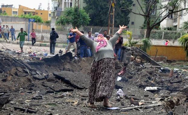 Mulher chora no local da explosão dos carros-bomba em Reyhanli, na Turquia (Foto: AP)