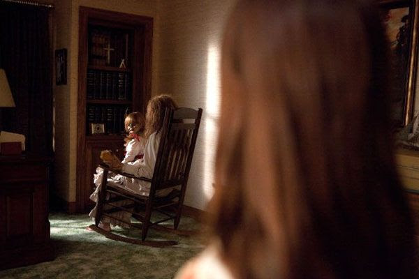 Sitting on the lap of Bathsheba the Witch, Annabelle the Doll turns to greet an unsuspecting visitor in THE CONJURING.