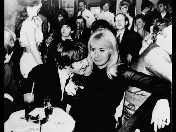 John Lennon, one of the Beatles, and his wife, Cynthia, are shown in a night spot after the visiting British Rock 'N' Rollers made their New York debut Sunday, February 11, 1964. Paul McCartney is behind Lennon.