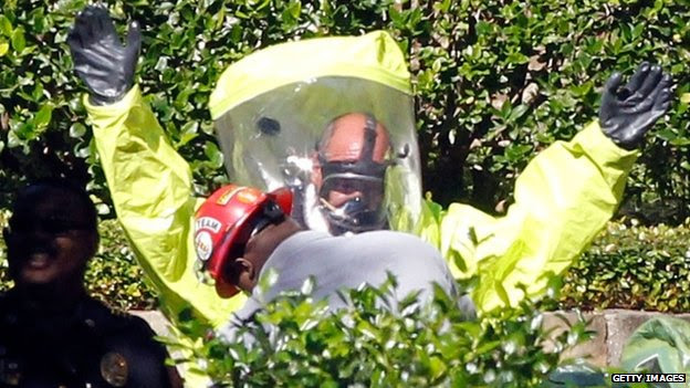 Hazmat workers help each other put on protective clothing before entering The Village Bend East apartment complex where a second health care worker who has tested positive for the Ebola virus resides on October 16, 2014 in Dallas, Texas.
